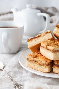 アップルジャムを詰めた自家製ショートブレッドクッキー。白いお皿に。グレーのリネンのテーブルクロスに。奥にはティーポットとカップ。