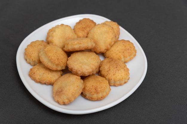 Домашнее песочное печенье на белой плите. выпечка к чаю. аппетитное печенье. серый фон.