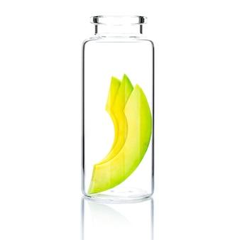 Домашний уход за кожей с ломтиком авокадо в стеклянной бутылке, изолированной на белом.