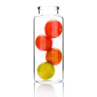 Домашний уход за кожей с помидорами черри в изолированной стеклянной бутылке на белом.