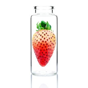 Домашний уход за кожей со свежей клубникой в стеклянной бутылке, изолированной на белом.