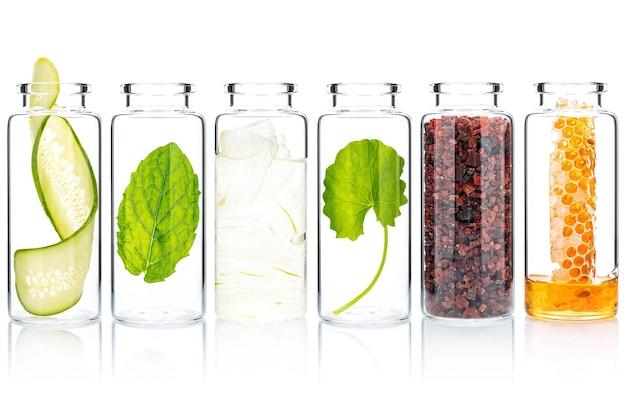 白い背景で隔離のガラス瓶に天然成分を使用した自家製スキンケア。