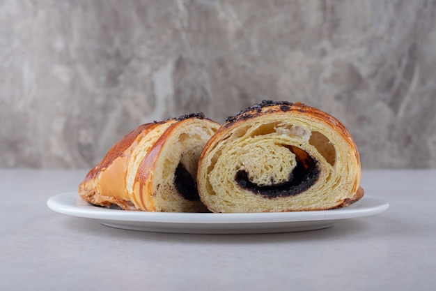 Homemade sliced croissant with chocolate on a plate on marble table.