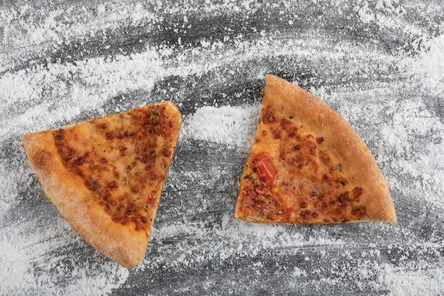 Pizza a fette fatta in casa su superficie nera con farina di frumento versata
