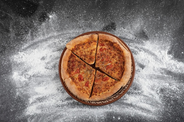 Домашняя нарезанная пицца на коричневой тарелке на черной поверхности