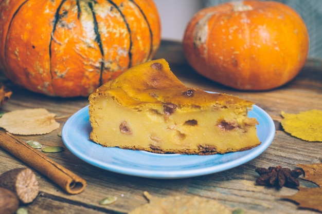 Homemade sliced pumpkin tart pie recipe with cinnamon, nuts on wooden background. halloween traditional dessert