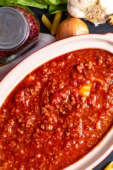 Homemade slow cooker bolognese sauce in red ceramic pot and raw penne