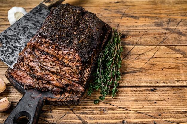 수제 훈제 바베큐 쇠고기 양지머리 고기. 나무 배경입니다. 평면도. 공간을 복사합니다.