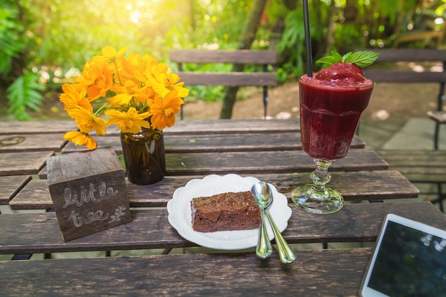 Homemade a smoothies and brownie cake on wood background.