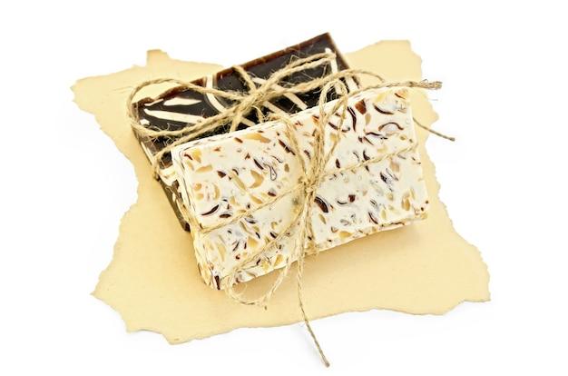 白い背景で隔離の古い紙の黄色い部分に自家製石鹸ベージュと茶色