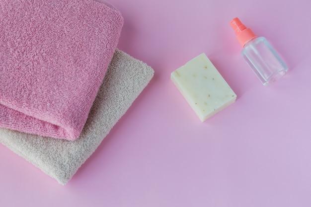 Домашнее мыло, жидкое антибактериальное дезинфицирующее средство для рук и розовые полотенца на светло-розовом фоне.