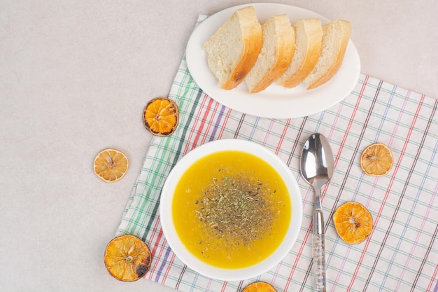 Домашний суп и кусочки хлеба на скатерти.