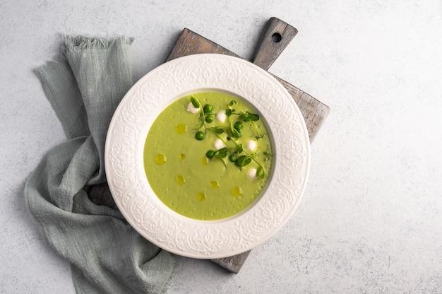 Homemade soup puree of green peas, coconut milk, mini mozzarella cheese in white plate wth napkin on