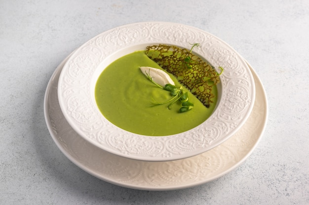 Homemade soup puree of green peas, coconut milk with tuil and cheese quenelle in white plate on
