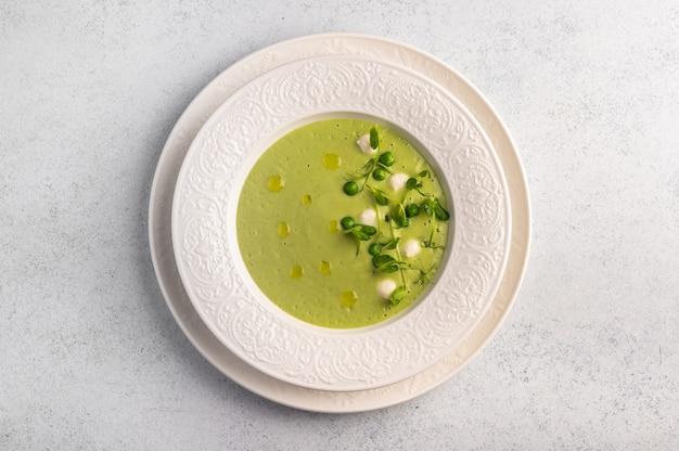 녹색 완두콩의 수제 수프 퓨레, 빛에 흰 접시에 미니 모짜렐라 치즈가 들어간 코코넛 밀크