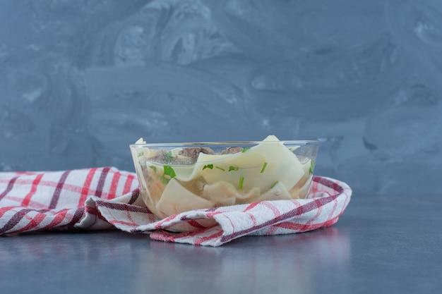 Zuppa fatta in casa con carne secca e pasta in una ciotola di vetro.
