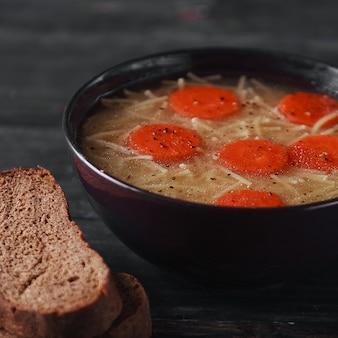 Домашний суп с ингредиентами морковной лапши на деревенском деревянном фоне