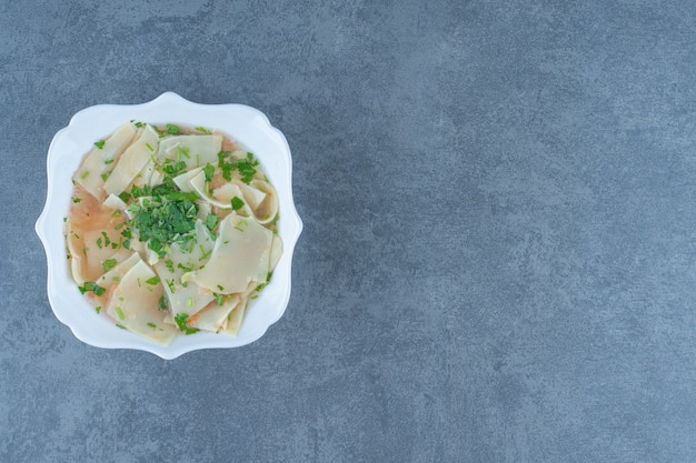 Домашний суп с макаронами в белой миске.