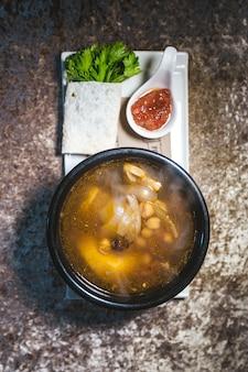 Домашний суп с горохом и мясом на подставке, вид сверху.