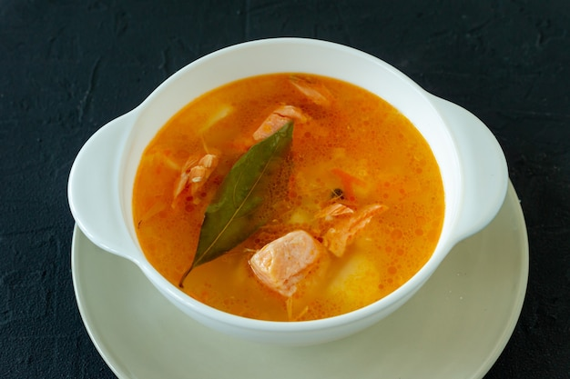 Homemade soup with salmon with bread sticks on back concrete