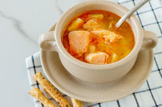 Домашний суп с лососем с хлебными палочками на мраморе