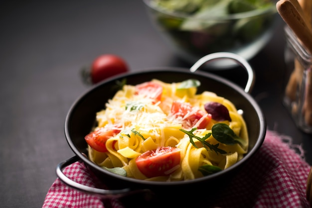 Homemade spaghetti pasta with grated cheese and cherry tomatoes in container