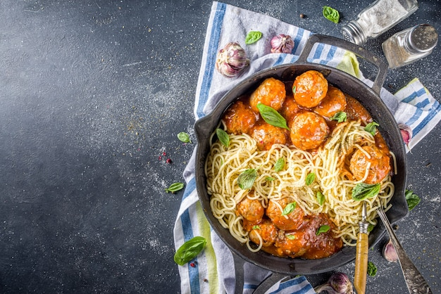 Homemade spaghetti pasta with meatballs in tomato sauce, dark concrete background above