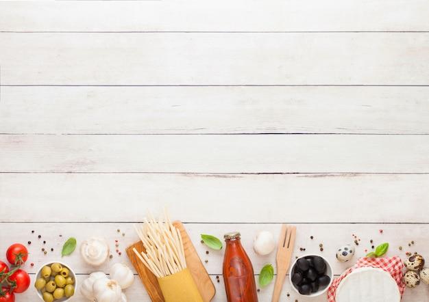 Домашняя паста спагетти с перепелиными яйцами с бутылкой томатного соуса и сыра. классическая итальянская деревенская кухня. чеснок, шампиньоны, черные и зеленые оливки, масло и шпатель