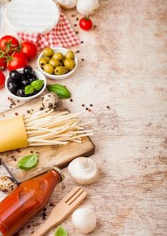 ウズラの卵とトマトソースとウッドの背景にチーズのボトルの自家製スパゲッティパスタ。伝統的なイタリアの村の食べ物。ニンニク、シャンピニオン、黒と緑のオリーブ、オイル、ヘラ