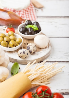 Домашние макароны спагетти с перепелиными яйцами с бутылкой томатного соуса и сыра на деревянный стол классическая итальянская деревенская кухня. чеснок, шампиньоны, черные и зеленые оливки