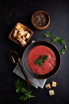 Homemade spanish tomato soup gazpacho with spice in black bowl
