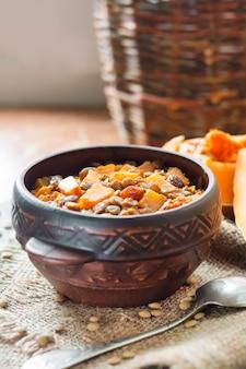 素朴なセラミックボウルにグリーンレンズ豆、カボチャ、レーズンを添えた自家製スパイシーカレー