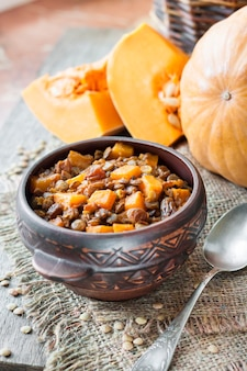 Homemade spicy curry with green lentils, pumpkin and raisins in rustic ceramic bowl