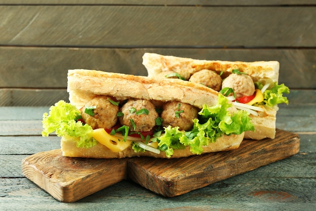 Homemade spicy meatball sub sandwich on wooden table background
