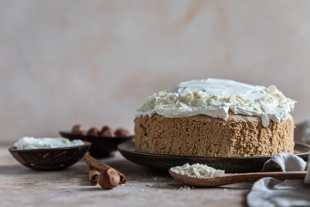 Homemade sponge cake or biscuit with nuts and spices with butter cream or cream cheese icing