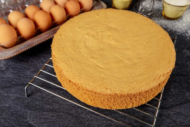 Homemade sponge cake on black background with brown eggs, flour and whisk. bakery concept.