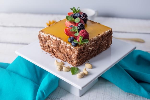 黄色のゼリーと明るい背景にミントとベリーの上に飾られた自家製の正方形のケーキ。