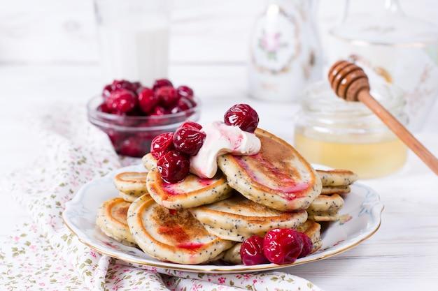 Домашняя стопка блинов с вишней на тарелке для вкусного здорового завтрака