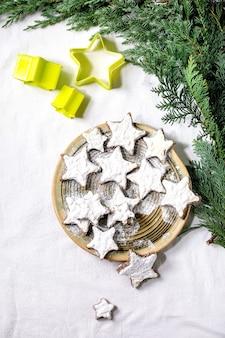 白い釉薬と粉砂糖を使った自家製の星型ココアアーモンドクッキー。クリスマスの星のクッキーカッター、thujaの枝、白いテーブルクロスの上の装飾が施されたセラミックプレート。フラットレイ、コピースペース