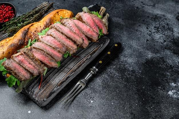 スライスしたローストビーフ、ルッコラ、チーズを使った自家製ステーキサンドイッチ。黒の背景。上面図。スペースをコピーします。