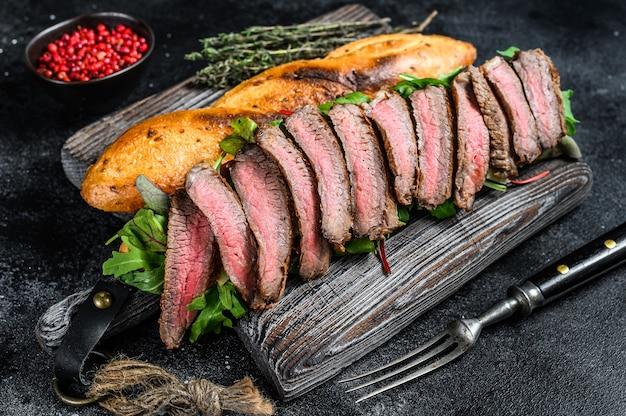 Homemade steak sandwich with sliced roast beef, arugula and cheese