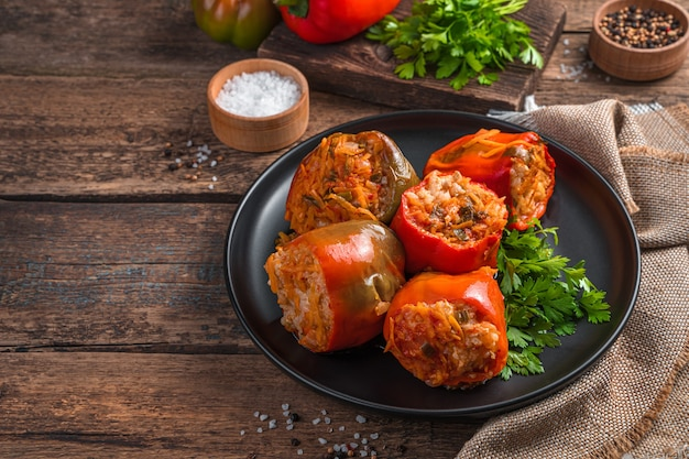Homemade stewed bulgarian pepper stuffed with meat rice and vegetables on a wooden background