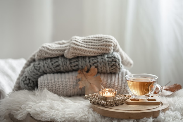 Homemade still life with knitted sweaters and a cup of tea on a blurred background.