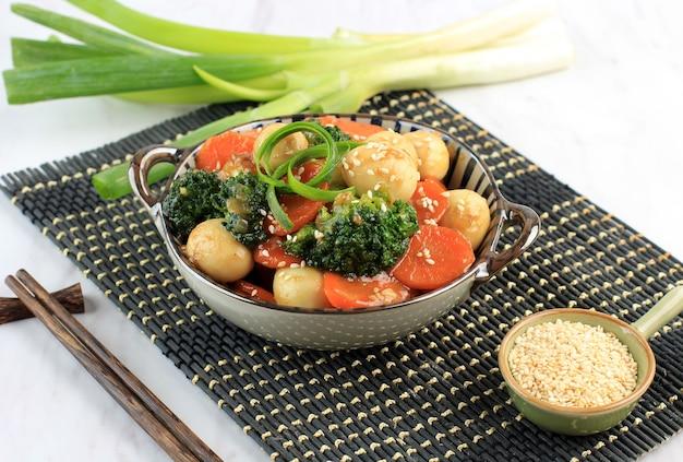 수제 메추리알을 굴 소스(telur puyuh saus tiram)에 야채와 함께 볶고 참깨를 얹습니다. 인도네시아에서는 capcay sayur telur puyuh라고 합니다. 세라믹 그릇에 제공