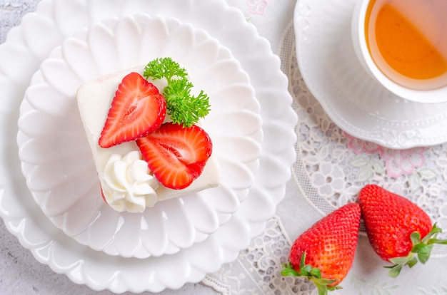 Homemade strawberry cake on a white plate with tea. top view.