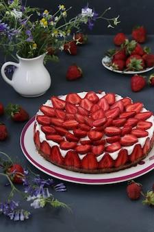 新鮮なイチゴで飾られた自家製のイチゴのチーズケーキ、暗い背景のプレート、垂直フォーマット