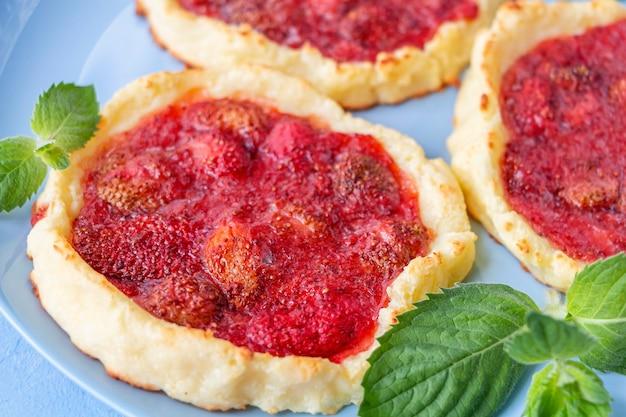 Домашняя клубничная тарталетка без глютена, ягоды, бисквит, летний десерт на синей тарелке, украшенная