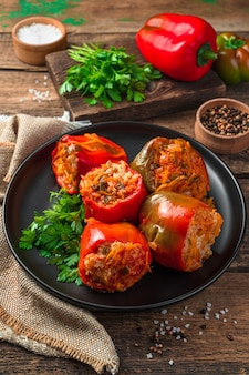 Homemade stuffed stewed bell pepper with turkey vegetables and rice on a wooden background