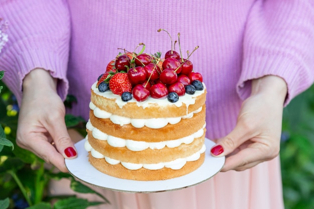 Homemade summer biscuit cake with cream and fresh berries in woman hands in the garden