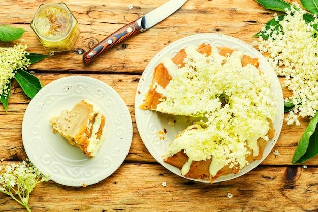 엘더 플라워로 장식된 수제 여름 케이크. 달콤한 소박한 케이크입니다.